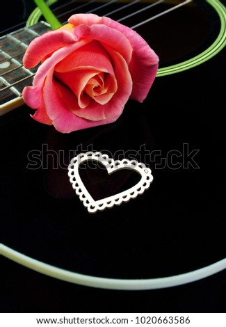 Heart of lovers, beautiful rose and black acoustic guitar. Symbols of love. Valentine's Day. #1020663586