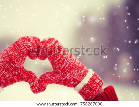 Heart of mittens in snow. Knitted gloves in winter #758287000