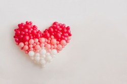 Heart of pink balloons on a white wall.