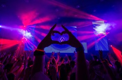 Heart of the hands silhouette on a concert in the center of the heart - DJ visible on the stage.Pink rays laser show.