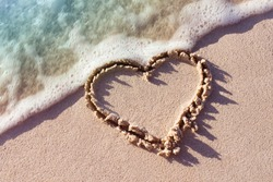 heart on a sand of beach with wave on background