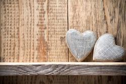Heart on a wooden shelf. Wooden wall, studio photography.