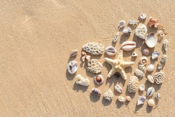Heart on sand. Coral parts, stones and shells arranged into a heart shape.