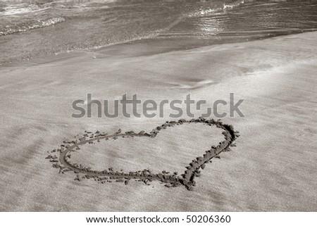 heart on sand on ocean beach