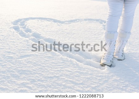 Heart on snow created by footsteps. Woman legs dressed in snow boots. Winter background. #1222088713