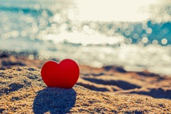 Heart on the sand on the summer beach with sea background. Close-up. Toned. Congratulations on saint valentine's day, greeting card