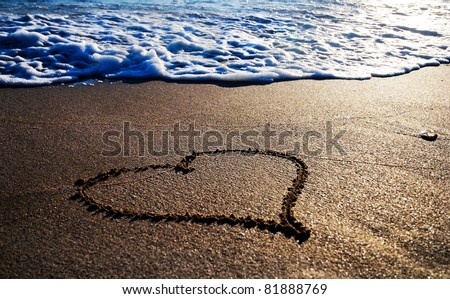 heart outline on the wet sand with the wave brilliance