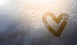 Heart painted on glass in Rainy weather, is fogged up and there are many drops on it, and the sun shines outside the window at dusk, toning in classic blue, banner with copy space,