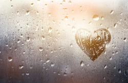 Heart painted on glass in Rainy weather, is fogged up and there are many drops on it, in a romantic pink tint, sunny sunset