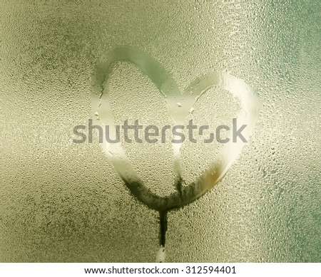 Heart painted on glass with rain drops #312594401