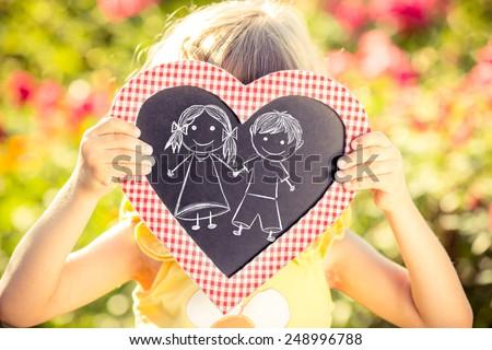 Heart shape blackboard with drawn children in hands against spring flower background