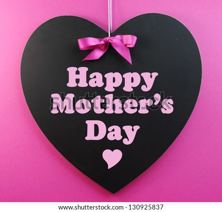 Heart shape blackboard with pink ribbon on pink background with Happy Mothers Day message.
