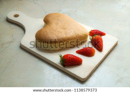 heart shape cheese cake with strawberry on wooden chopping board for valentine's day