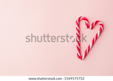 Heart shape Christmas candy on pink background with copy space, seasonal love minimal concept, sweetness, romance, holiday