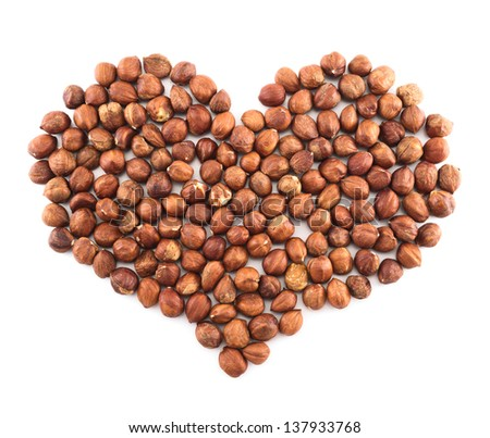 Heart shape composition made of hazelnuts isolated over white background