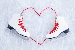 Heart shape created from bright red shoelaces. White female figure skates on ice background. Closeup. Empty place for motivational, inspirational text, quote or sayings.