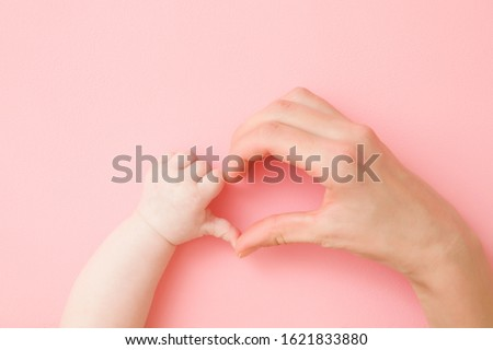 Heart shape created from infant and young mother hands on light pink table background. Pastel color. Lovely emotional, sentimental moment. Love, happiness and safety concept. Closeup. Foto d'archivio ©