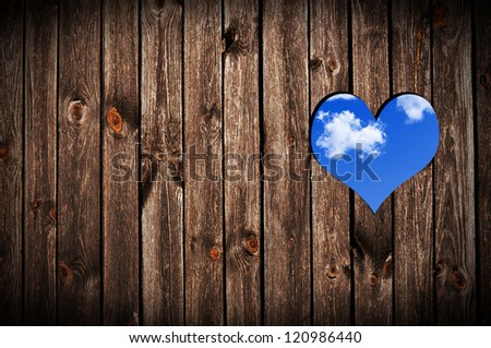 Heart shape cut on wooden wall.
