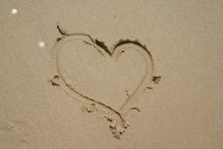 Heart shape draw on the beach sand