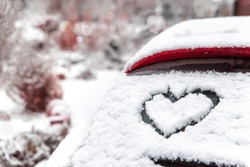 Heart shape drawn by hand on car window covered with fresh snow. Frozen rear windshield with heart on winter day