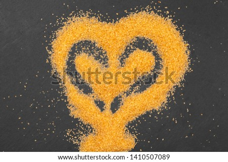 Heart shape drawn on granulated sugar as a background