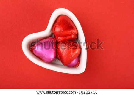 Heart shape foil wrapped chocolates in a heart shape white bowl on red textured paper background