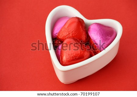 Heart shape foil wrapped chocolates in a white heart shape bowl on a red textured paper background