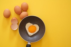 Heart shape fried egg in the pan with egg shell and chicken eggs on yellow background. top view. healthy food  concept. Copy space for text