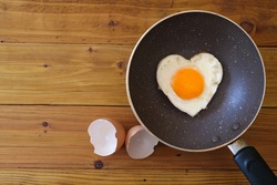 Heart shape fried egg in the pan  with egg shell on wooden background. top view. Valentine's day celebration. healthy food  concept.