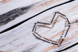 Heart shape from construction tools on wooden background.