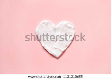 Heart shape from cream in pink background. Skin care.