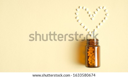 Heart shape from pills pilling from a glass bottle. Pharmacy store, medical clinic, drugstore banner design template. Medical tablets, drug of painkillers, antibiotics, vitamins. Flat lay, top view Stock photo ©