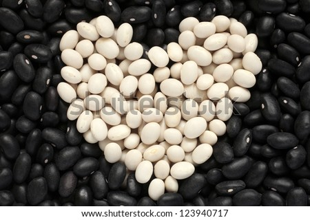 Heart shape from white haricot beans on black haricot beans background, a horizontal picture