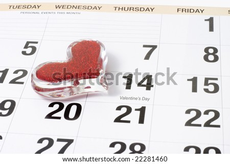 Heart shape glass paper weight on calendar page showing February 14 Valentine's Day