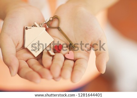Heart shape home key with house keyring and mini heart figure on kid's hand to giving, sweet valentine home present giving concept, soft color tone, copy space, copy space #1281644401