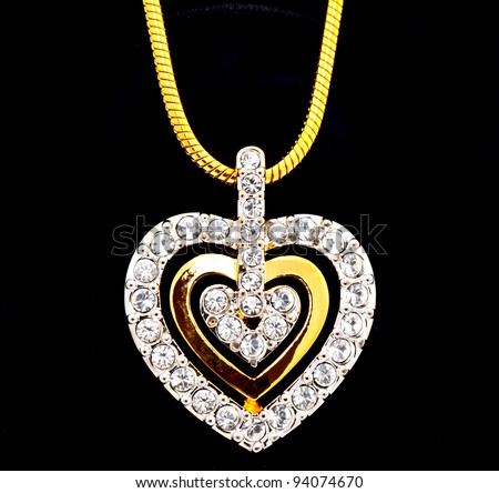 heart shape locket and gold chain decorated with diamonds, studio shot