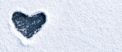 Heart shape love sign, drawn on a snow-covered ice on a winter lake with copy space. Romantic backdrop.