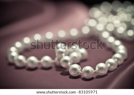 Heart shape made from pearls on the red satin