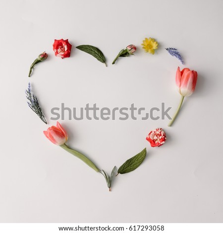 Heart shape made of colorful spring flowers and leaves. Flat lay. Love concept. #617293058