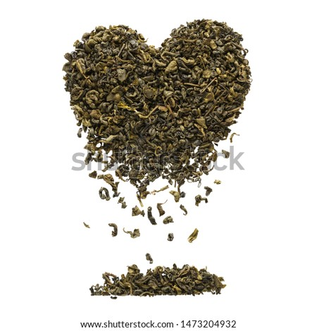 Heart shape made of dry Oolong tea leaves. Tea leaves falling down. Isolated on white background.