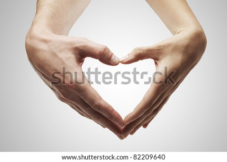Heart shape  made of  female and male hands together.Isolated on a gray background