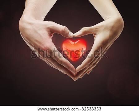 Heart shape  made of  female and male hands together.With a red heart inside.