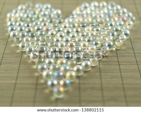 Heart shape made of transparent glass balls over bamboo mat as abstract background