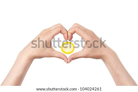 heart shape made of two beautiful palms with condom on white background