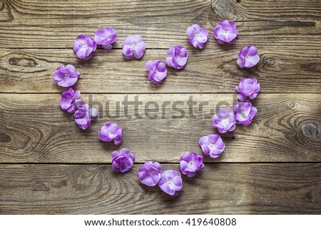 Heart shape made of violet flowers on grunge wooden boards. Place for text. Top view with copy space.