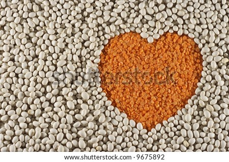 Heart shape made with red lentils and surrounded with haricot beans healthy eating.