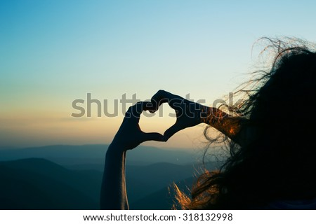 Heart shape. Mountain tourism. Symbol of love. Manifestation of love. Expression of feelings. Enjoy. Girl on a background of mountains. Love and feelings. Long red hair. Wind blowing through her hair.