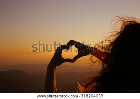 Heart shape. Mountain tourism. Symbol of love. The manifestation of love. Expression of feelings. Love of nature. Girl on a background of mountains. Love and feelings. Wind blowing through her hair.