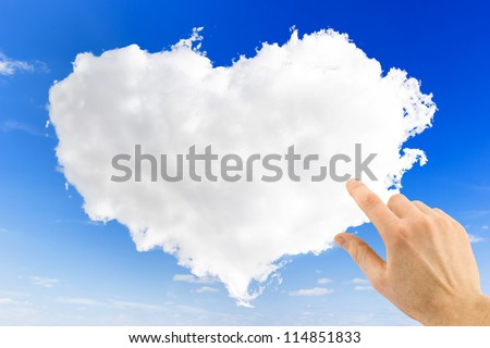 heart shape of cloud and hand point on it over blue sky background