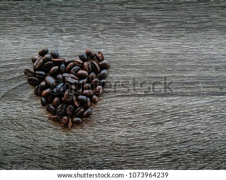 heart shape of coffee bean on wood table background.